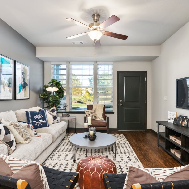 Authentix apartment interior with couch, circular coffee table, window, and exterior door